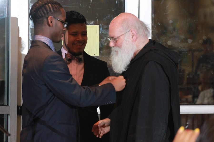 Fr. Augustine Curley, O.S.B., as Newark Abbey's archivist, provided invaluable research to student journalists. (From left) Editor-in-chief Jules-Roland Gouton says thank you. Jacob Amaro is at center.
