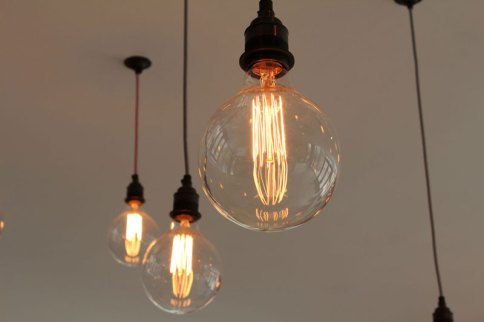 Filament lamps suspended over seating areas.