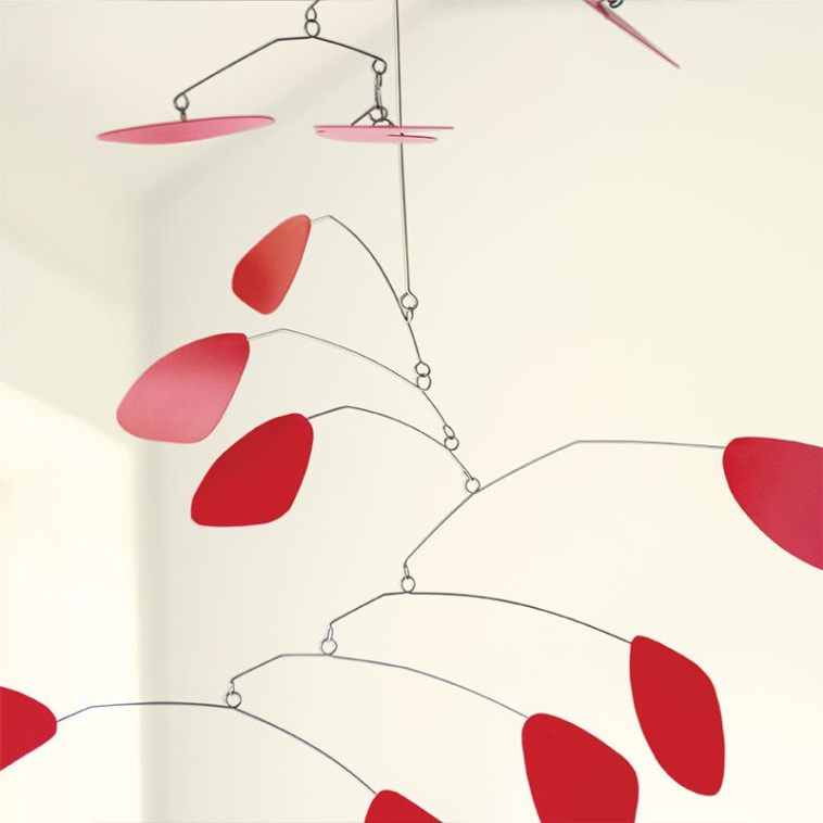 A delicate red mobile is elegant yet striking against white walls.