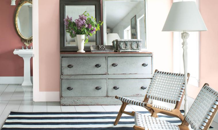 A pink-hued bedroom with angled ceiling and grey bureau features a a seating area with two contemporary chairs and a glimpse into the powder room