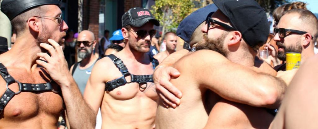 Gay men at pride parade in fetish wear harness