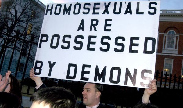 Crazy religious man holding homophobic sign