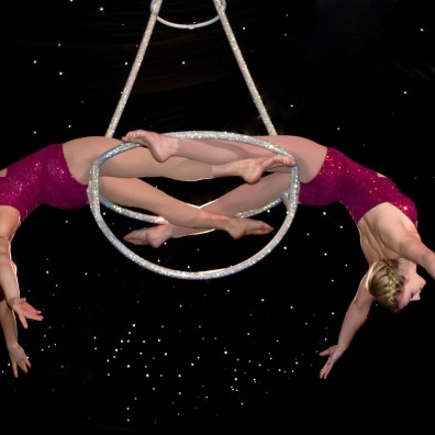 Aerialist duo act performing in matching red costumes