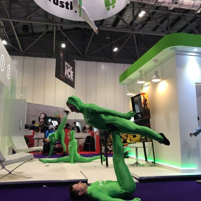 Acrobats and circus acts in green suits perform on exhibition stand