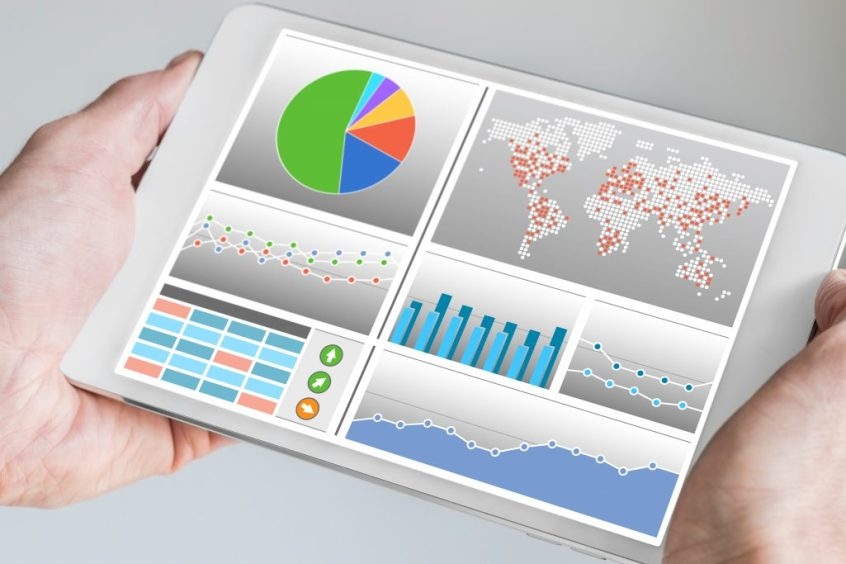 Hand holding modern tablet or mobile device with analytics dashboard for sales, marketing, accounting, controlling department to check revenue, sales and business KPIs