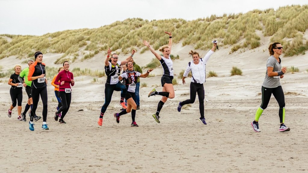 Berenloopsters van Team Anita springen een gat in de lucht op het strand tijdens de Berenloop 2017.