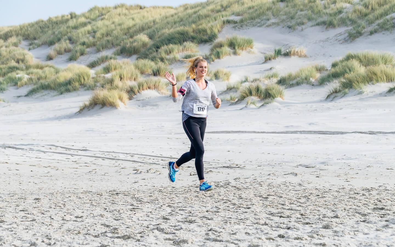 Berenloopster op het strand tijdens de halve marathon van de Berenloop 2018.