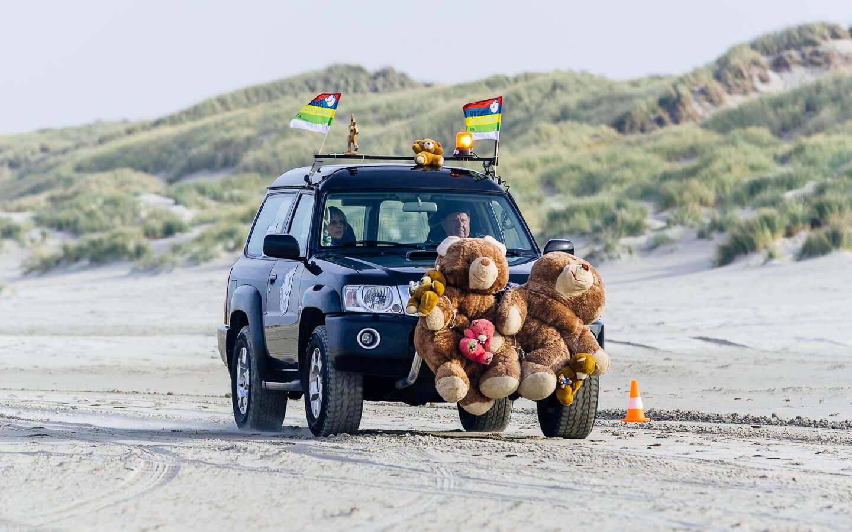 Auto van de organisatie met de beren voorop op het strand tijdens de Berenloop 2018.