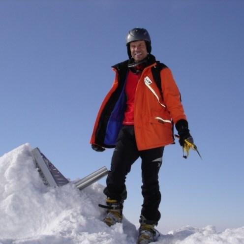 Ich alleine neben dem zugeschneiten Gipfelkreuz