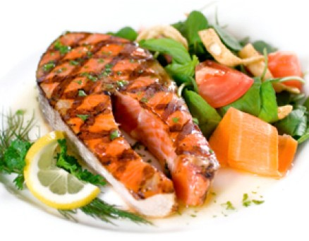 Delicious salmon steak grilled to perfect and served with a colorful side salad of wild greens. Shallow dof.