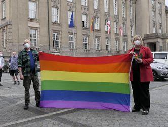 Bildvergrößerung: 2 Personen halten eine Regenbogenfahne hoch.