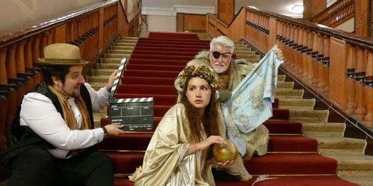 Drei Personen sitzen auf einer Treppe.  Links sitzt ein Mann und ist dabei, eine Klappe zu schließen.  Rechts eine Frau mit goldenen Rosen im Haar und einer goldenen Kugel in der Hand und ein Mann mit Augenklappe und Weltkarte.