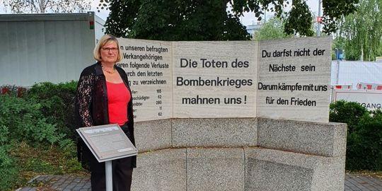 """Eine Frau steht neben einem steinernen Denkmal mit der Aufschrift """"Die Toten des Bombenkrieges ermahnen uns!"""".  Vor ihr ist eine kleine Informationstafel aufgestellt."""