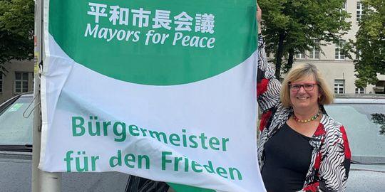 """Eine Frau hält an einer Stange eine Fahne mit der Aufschrift """"Bürgermeister für den Frieden"""" hoch."""