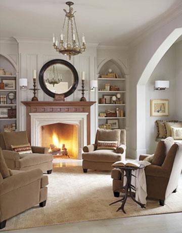 Schöner sitzen: Weiße Wände, offener Kamin und Sessel in Greige