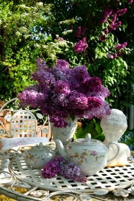 Ulli hat ein Händchen für schöne Dekorationen. Überall im Garten gibt es Sitzgruppen, die sie schmückt wie hier mit Flieder und nostaligischem Porzellan