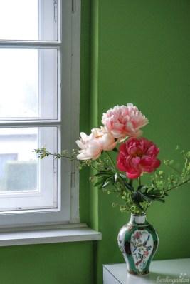 Im grünen Salon kommen die strahlenden Blüten und die Vase im chinesischen Stil besonders zur Geltung