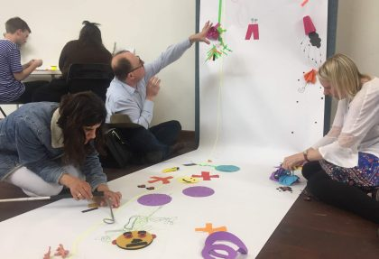 One man and two women attaching on a white paper roll colorful objects made of different materials