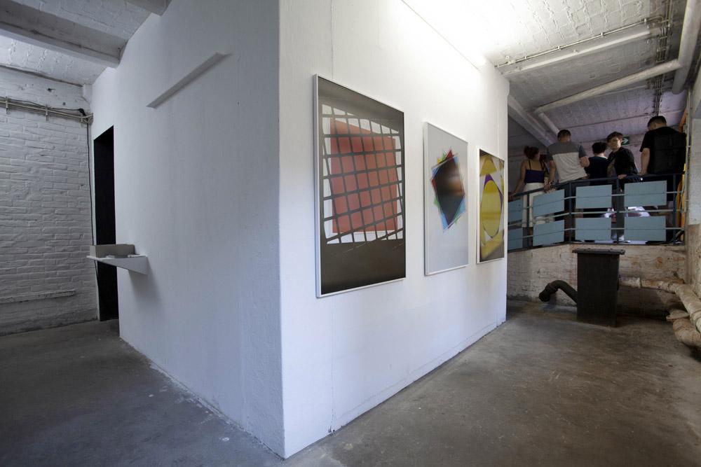 Drei große farbige Bilder im Hochformat hängen nebeneinander an einer weißen Wand. Im Hintergrund Personen auf einer Rampe.