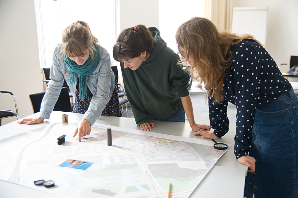 Three persons leaning on a table looking at a city map laying on the table with diverse objects standing on on top of it