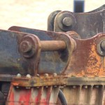 three rusted industrial parts