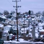 neighborhood on hill in snow at dusk