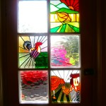 stained glass panels in front door of cerdyn villa, a comic strip of the life of a chicken