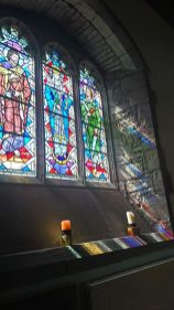 sunlight streaming through the stained glass of St Gwedolines Chrch