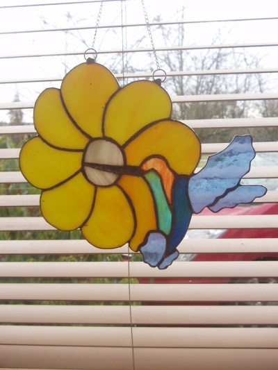 stained glass suncatcher of humming bird drinking nectar from a flower