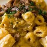 Macaroni met de vegan kaassaus en seitan spek in blokjes er over