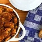 witte ovenschaal met deksel gevuld met vegetarische boboti met houten opscheplepel op keukenhanddoek