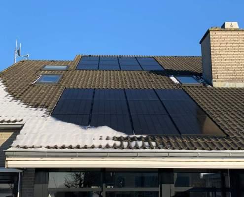 Dak met sneeuw en zonnepanelen