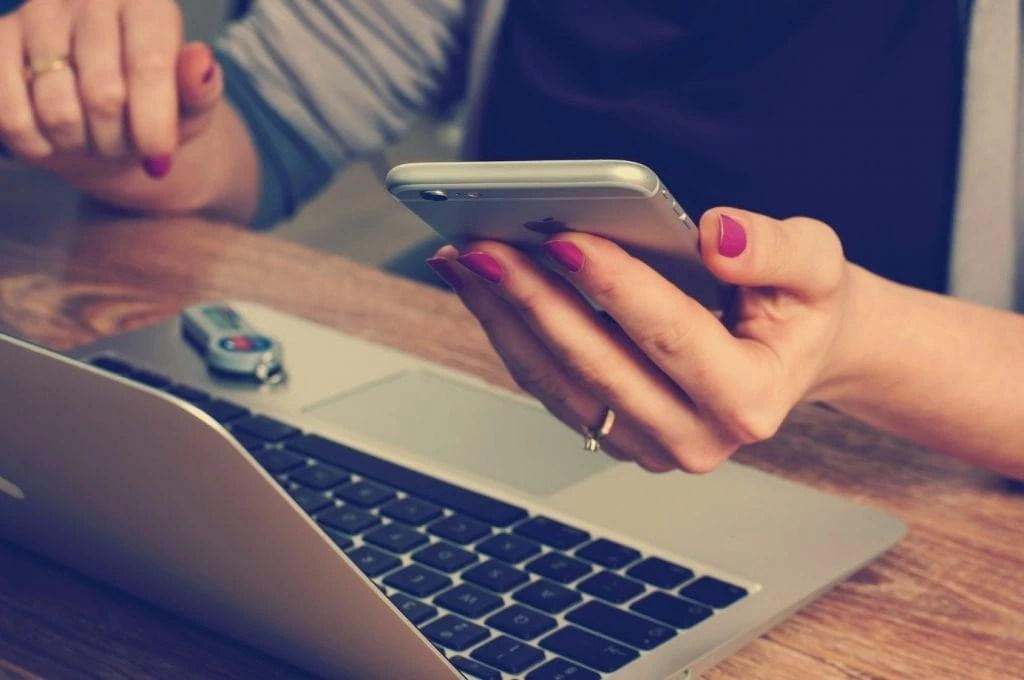 Frau hält Smartphone in ihrer Hand und sitzt mit Laptop an Schreibtisch.