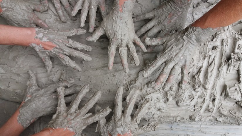 Variety of hands covered in mud
