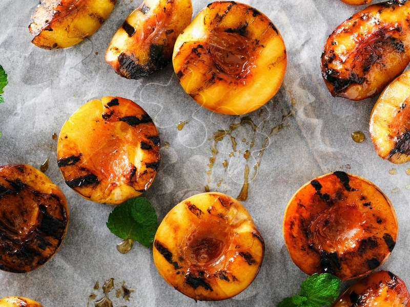 Top view grilled peaches served with mint leaves on paper. Copy space