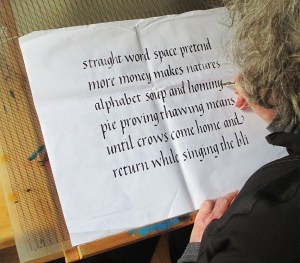 Calligraphy artist and workshop teacher Pam Galvani touching up her italic calligraphy in pen and ink
