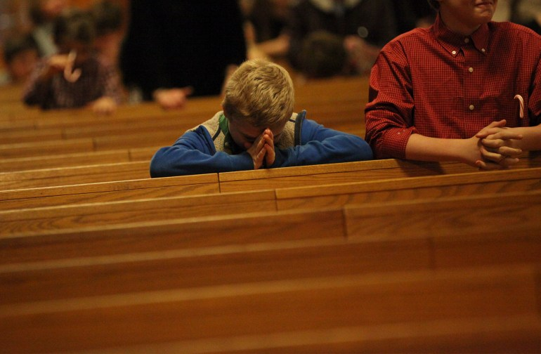 Shea Morley, from Scituate, says a prayer during Communion while sitting next to his cousin Justin Beresford, Scituate. St. Francis X Cabrini holds what may be the final service at St. Francis on Christmas Eve, Dec. 24, 2015. Wicked Local Staff Photo/Alyssa Stone