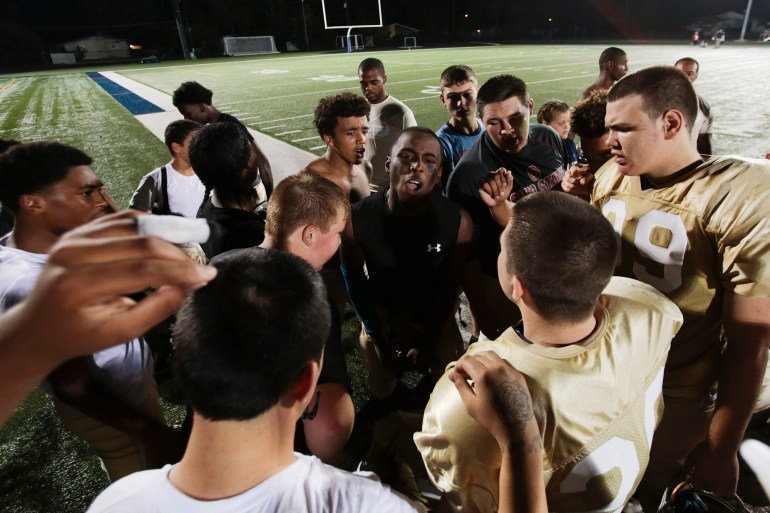 Jay Davis, center, rallies his team following their 77-0 loss to Bishop Hartley. The Thunder would go on to lose all their games this season, finishing 0-8, while Hartley would go on to claim a state championship.
