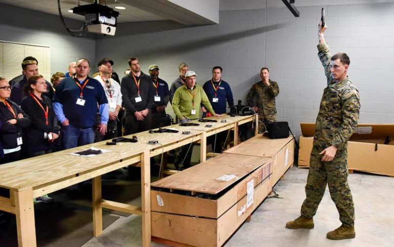 Marine Erik Walker, primary marksmanship instructor, gives a demonstration on how to use an Beretta firearm, to teachers from around New England when they got a chance to see what life would be like for Marine recruits during the Marine Corps Educator Workshop at Parris Island in South Carolina on Wednesday, Feb. 25, 2015.