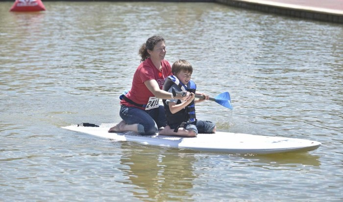 Angie Pinkerton and her son Noah Pinkerton , 6, have some fun on a stand up paddle at the Under Water Connection during the Boat Bands and BBQ held on the HARP Riverwalk in Pueblo Colo. on June ,6,2015. (John Jaques,The Pueblo Chieftain)