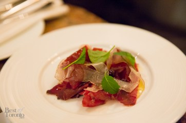 "house-cured, air-dried Bison ""Pemmican"" Bresaola is thinly shaved and paired with house-made lardo, lightly dressed with Chef's wild blueberry juniper vinaigrette"