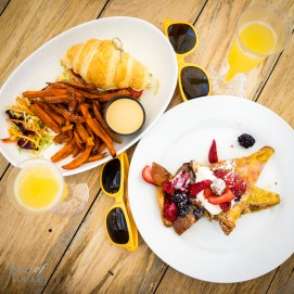 Left: Peameal bacon and fried egg sandwich with O&B artisan butter croissant, lettuce, tomato, avocado mayo, sweet potato fries Right: Cinnamon brioche french toast with seasonal fruit, chantilly, candied pecans, local syrup