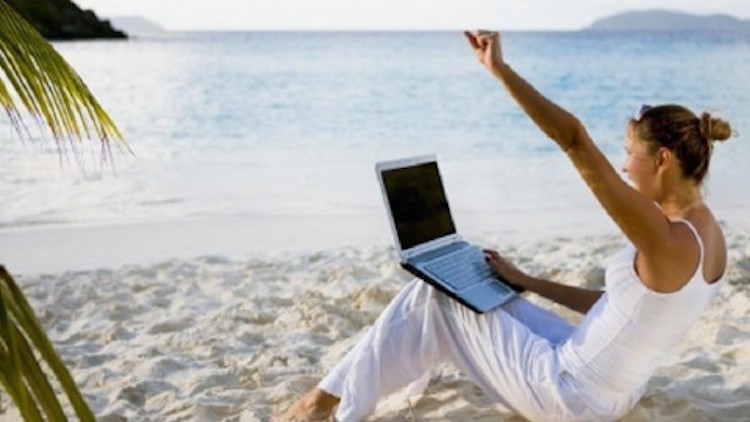 Woman using laptop on the Beach