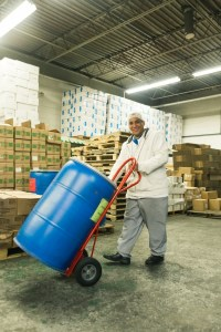 man pushing hand truck with plastic drum