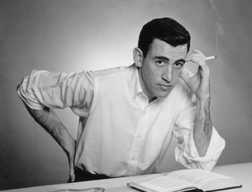 """NEW YORK - NOVEMBER 20, 1952: Author JD Salinger poses for a portrait as he reads from his classic American novel """"The Catcher in the Rye"""" on November 20, 1952 in the Brooklyn borough of New York City. Salinger died on January 27, 2010. (Photo by Antony Di Gesu/San Diego Historical Society/Hulton Archive Collection/Getty Images)"""
