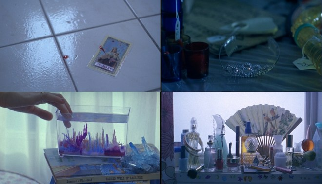 A still from the Virgin Suicides of the Lisbon sisters bedroom, showing a tiara, a fish tank, a prayer card, perfume and a fan.