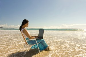 woman writing on laptop in ocean