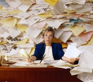 clutter-woman surrounded with papers