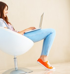 Woman in orange shoes writing on laptop