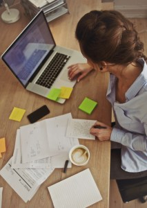 Woman writing on laptop with sticky notes and coffee